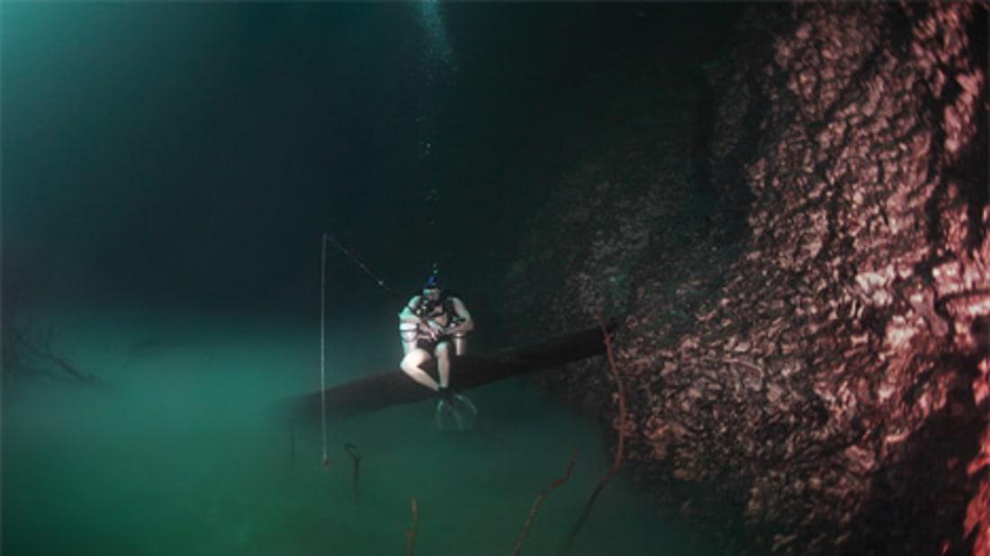 Thợ lặn câu cá dưới sông ngầm. Ảnh: Anatoly Beloshchin