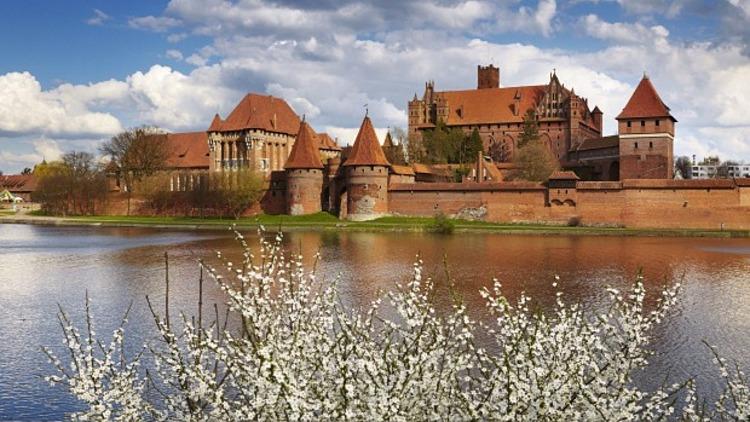 Tầm nhìn chiêm ngưỡng lâu đài đẹp nhất là từ bên kia sông, đặc biệt là vào buổi chiều muộn, khi gạch chuyển sang màu nâu đỏ đậm dưới ánh hoàng hôn. Ảnh: Traveller