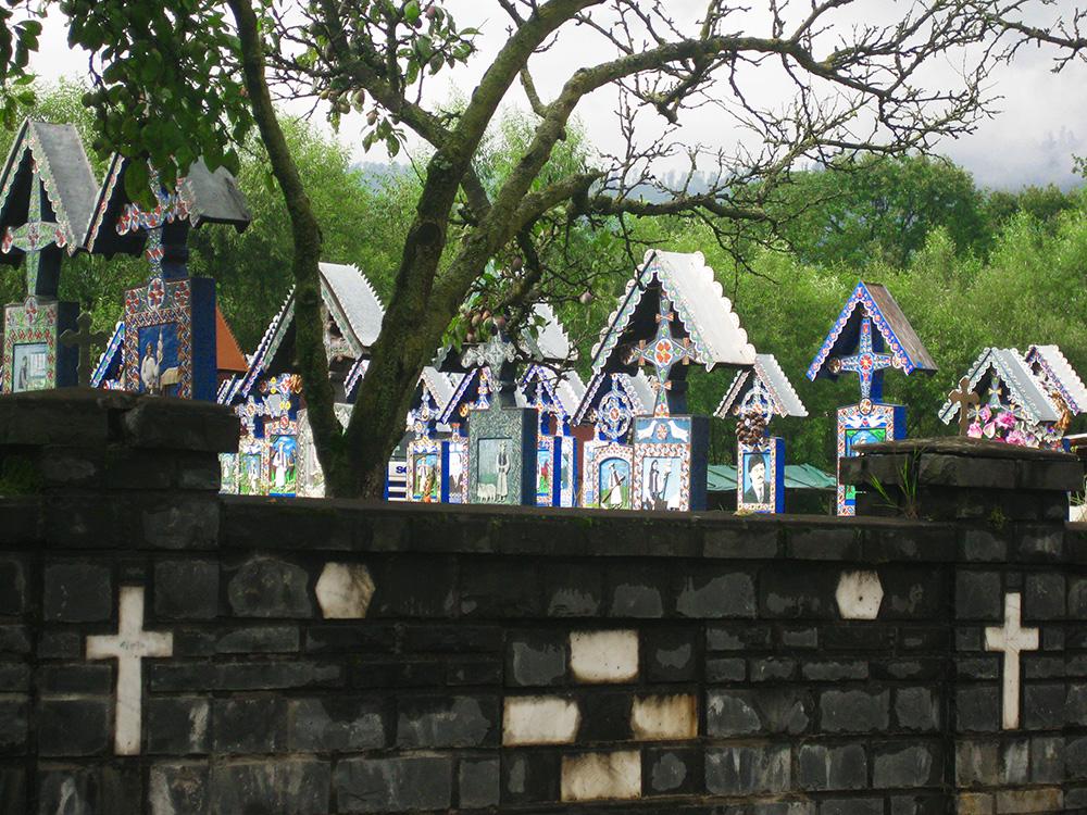 [Nghĩa trang Merry ở làng Sapanta là nơi có hơn 1.000 ngôi mộ với những cây thánh giá được khắc tinh xảo cùng bia văn đầy màu sắc cùng các nét vẽ hoạt hình. Sapanta là một ngôi làng nhỏ, chính vì vậy mà không có bí mật nào được giấu kín trong cộng đồng bé nhỏ này. Và những sai lầm mắc phải của người còn sống, đôi khi có thể đều được thể hiện lại qua những vần thơ, nét vẽ khắc trên bia mộ khi họ còn sống. Ảnh: Fear less female travels