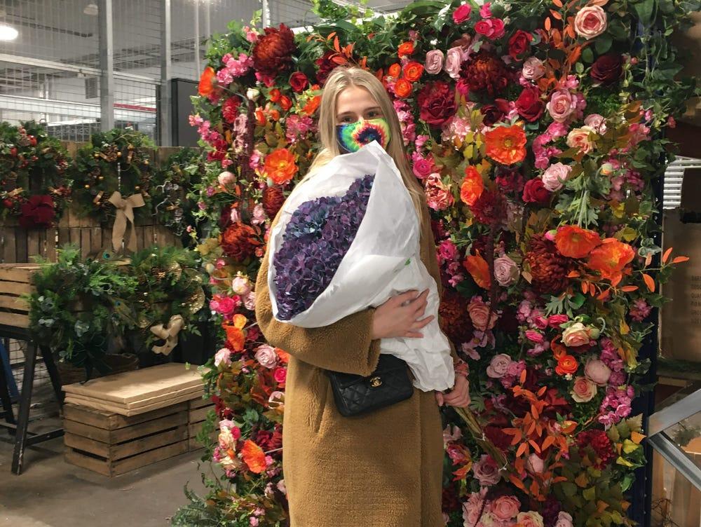 Johnston đến chợ từ rất sớm và rời đi trước khi mặt rời mọc. Trên ảnh, cô đang tạo dáng cùng một bức tường hoa. Ảnh: Insider