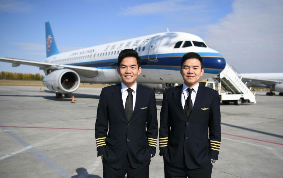 Trên ảnh là hai anh em sinh đôi Liu Ke (trái) và Liu Xin, chụp ảnh gần một chiếc máy bay của China Southern Airlines vào ngày 16/10/2018. Ảnh: Zhang Yao/China News Service