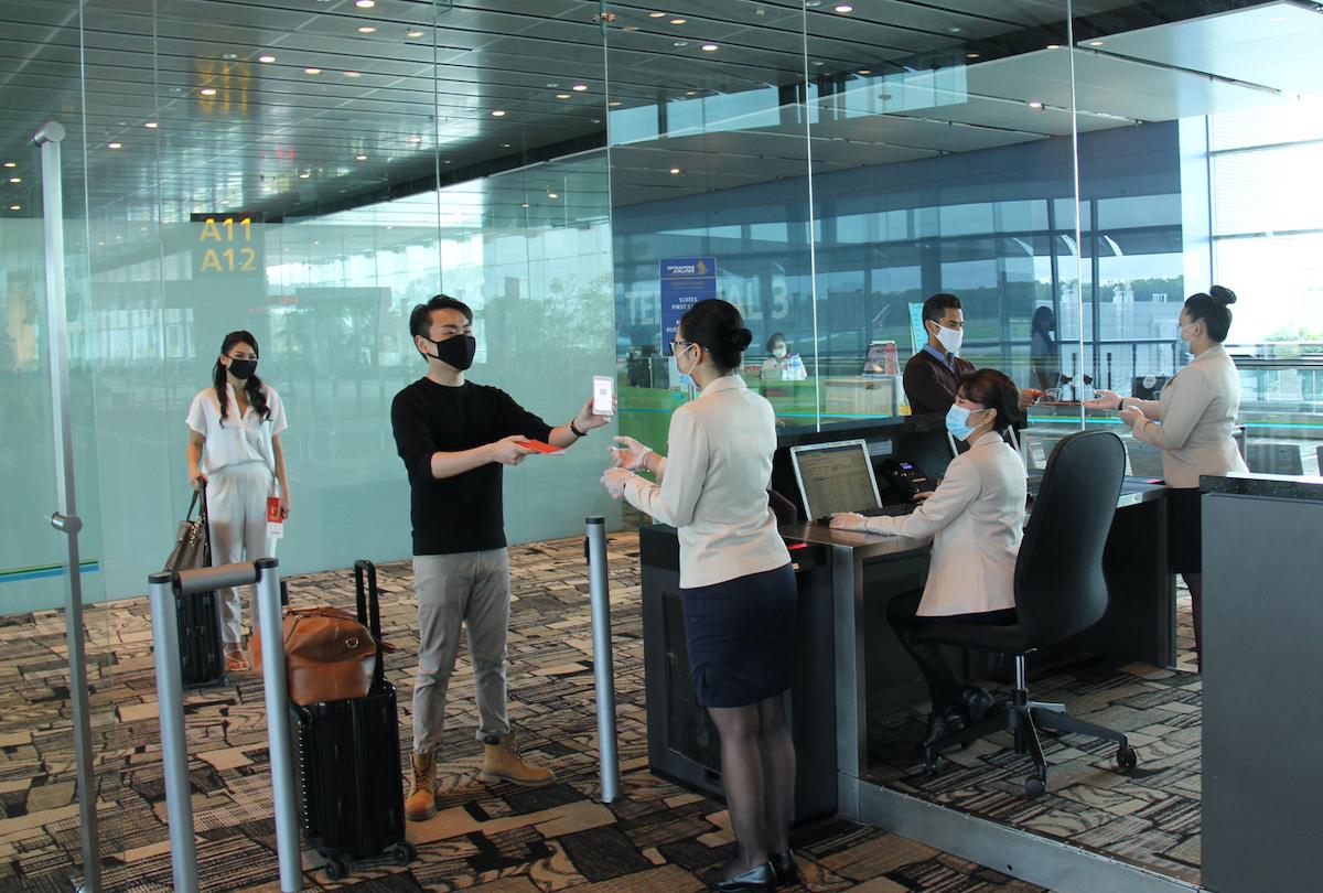 Hành khách giữ khoảng cách an toàn khi làm thủ tục tại quầy dịch vụ của Singapore Airlines. Ảnh: Singapore Airlines.