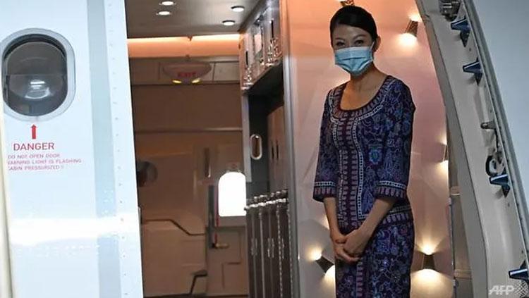 Một tiếp viên của hãng Singapore Airlines đeo khẩu trang trong suốt quá trình đón khách hôm 24/10. ẢNh: AFP