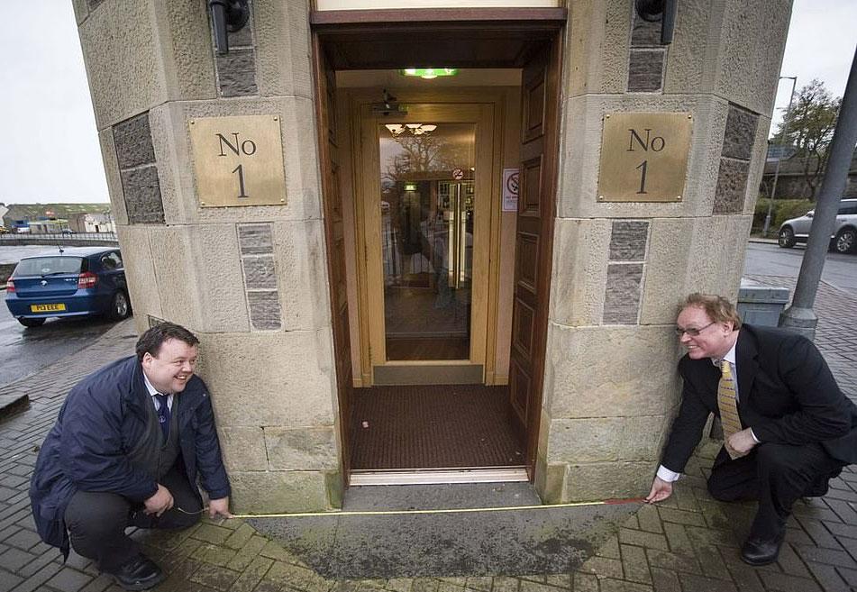 Craig Glenday (trái), tổng biên tập của sách kỷ lục Guinness thế giới, đo chiều dài con phố cùng chủ khác sạn Mackays, Murray Lamont. Ảnh: Northern Studios