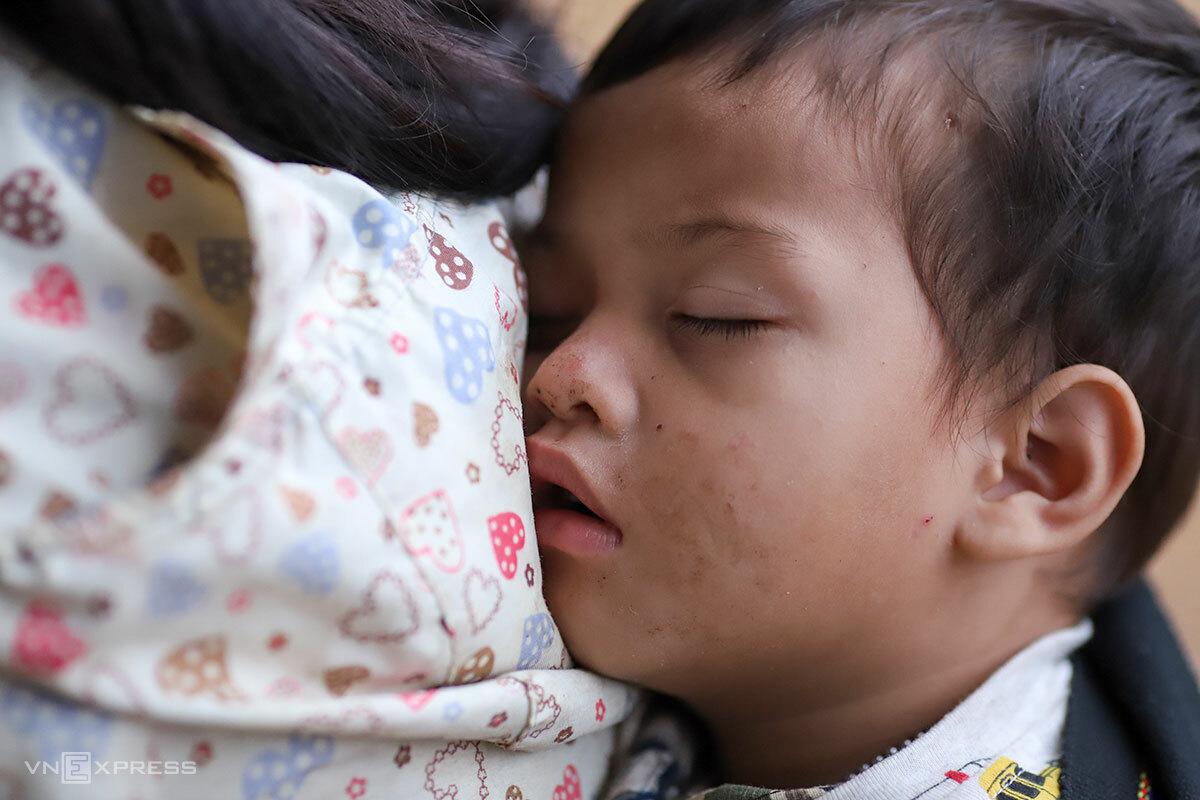 Bé Thiên ngủ thiếp đi trên lưng bà nội. Ảnh: Nguyễn Đông.