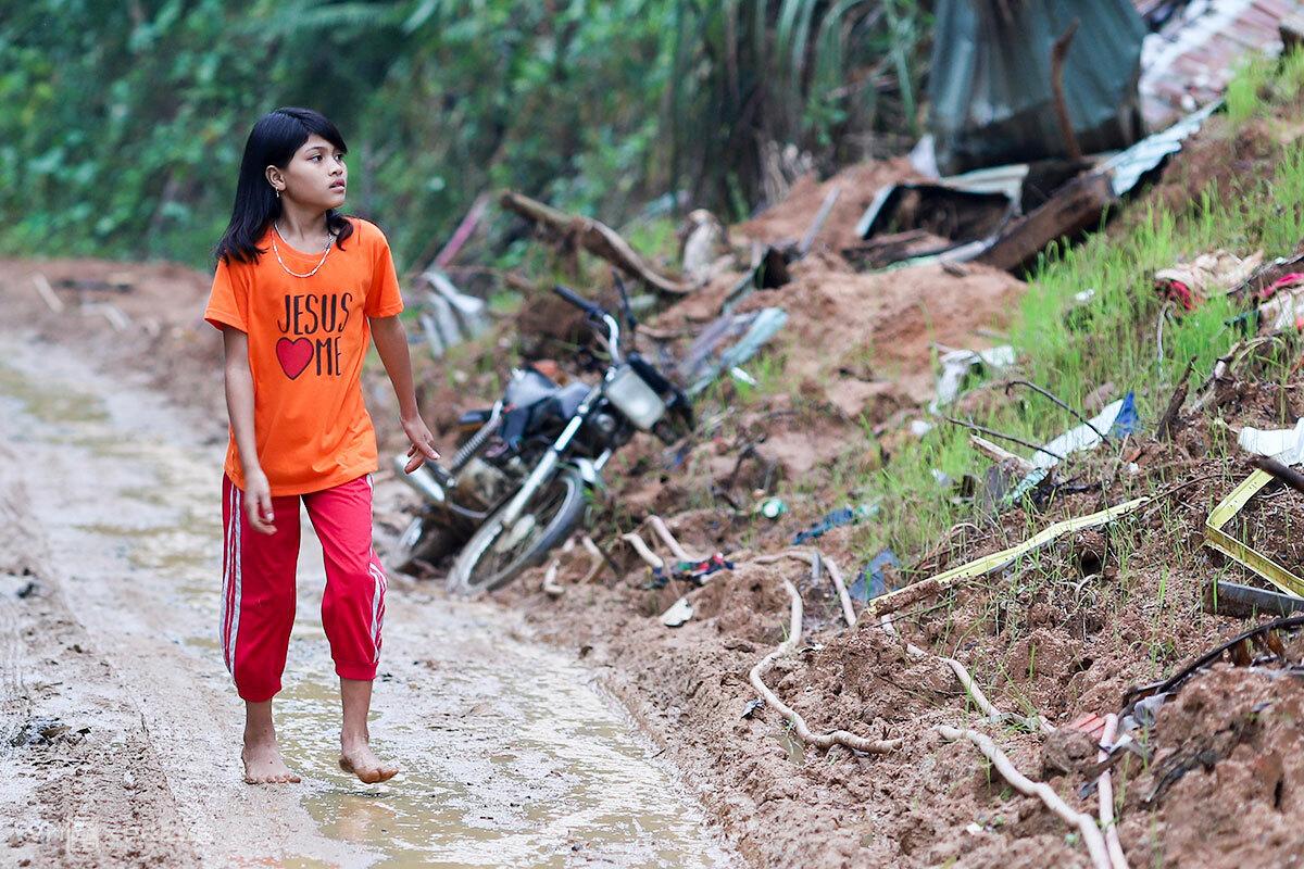 Hằng đi qua đống đổ nát trước đây là nhà mình. Ảnh: Nguyễn Đông.