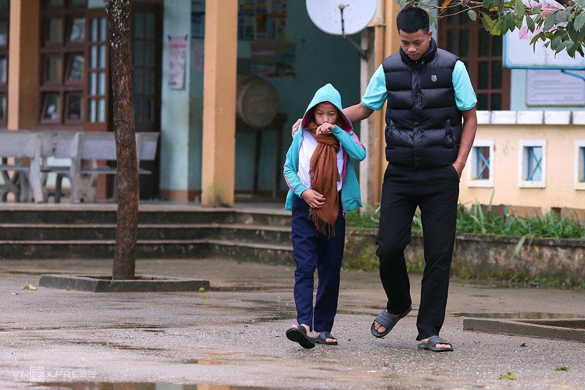 Hồ Thị Côi vẫn đi lại khập khễnh, thầy cô thường phải đi cùng để hỗ trợ. Ảnh: Nguyễn Đông.