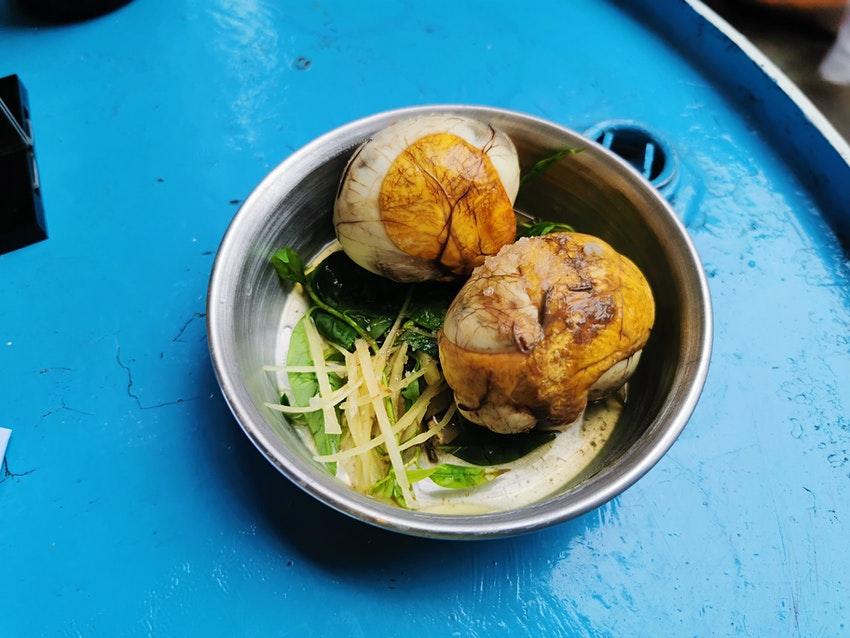 Trứng vịt lộn luộc có thể bóc trần ăn kèm với rau răm, gừng tươi xắt nhỏ. Ảnh: Fabienne Fong Yan