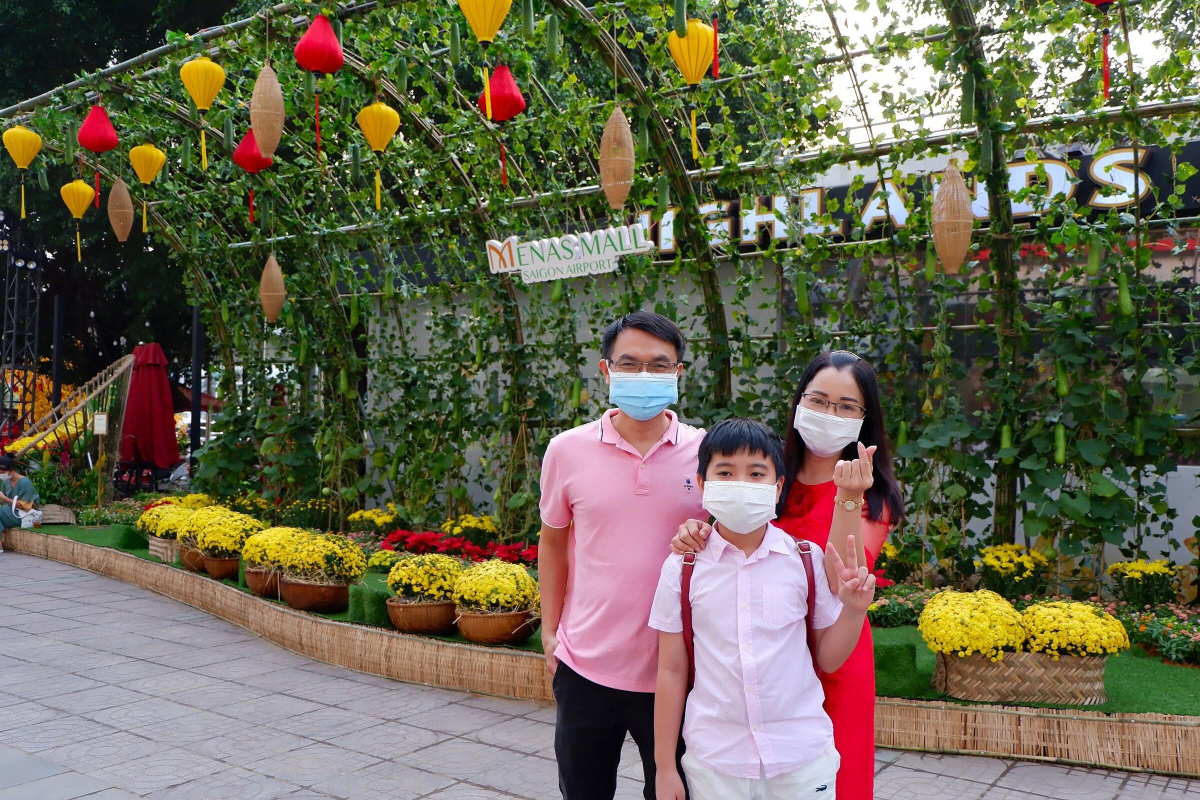 Ngày cận Tết, gia đình anh Hùng quyết định đổi trả vé máy bay để ở lại Sài Gòn. Ông bà nội của bé buồn lắm khi nghe tin này, nhưng họ hiểu và động viên gia đình nhỏ của tôi ăn Tết vui vẻ, anh kể. Trên đường về, anh đi ngang Menas Mall Saigon Airport, thấy có đường hoa trang trí đẹp mắt, anh Hùng quyết định đưa vợ và hai đứa con nhỏ ghé chụp ảnh kỷ niệm.  Trong hình là gia đình chị Hoàng Nguyệt ghé đường hoa tham quan. Ngó sơ đã thấy xuân vào tận cửa rồi. Vừa có dịp ngắm hoa cùng cả nhà, vừa có dịp mua sắm ăn uống, mình rất thích, chị chia sẻ.