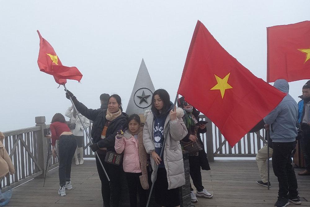 Du khách mang cờ tổ quốc lên đỉnh Fansipan. Ảnh: NVCC