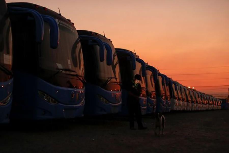 Một nhân viên bảo vệ đứng cạnh hàng xe buýt từng chở khách Trung Quốc đi khắp Thái Lan. Ảnh chụp trong một bãi đậu xe gần sân bay Suvarnabhumi ở Bangkok, Thái Lan ngày 5/2. Ảnh: Jorge Silva/Reuters