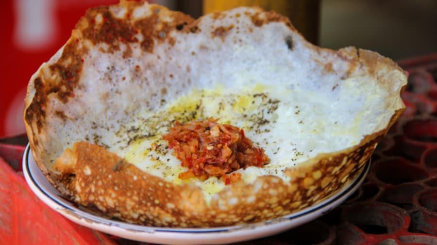 Một món điểm tâm sáng khác thường là appam (bánh kếp gạo nhúng nước cốt dừa) và idiyappam (bánh kếp sợi) của Sri Lanka. Bánh appam (ảnh) được làm từ bột gạo lên men trộn nước cốt dừa đem chiên lên thành hình một chiếc bát nhỏ, ở giữa có quả trứng, ăn kèm sambal (tương ớt dừa cay) hoặc sốt cà ri. Ảnh: Mark Wiens/CNN