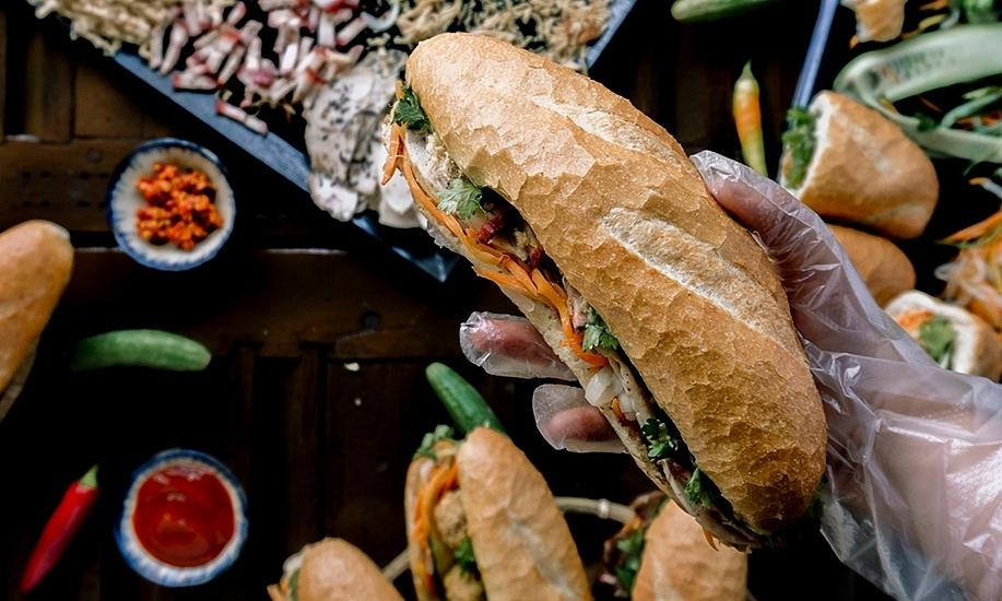 Bữa sáng được SCMP lựa chọn ở Việt Nam để giới thiệu với du khách quốc tế là bánh mì - được miêu tả là quả bom mang hương vị Pháp Việt. Món ăn này gồm bánh mì ăn kèm với pate, sốt, chả lụa, xúc xích, rau thơm, dưa chuột... được bày bán trên các quầy hàng khắp Việt Nam. Baguette phiên bản Việt cũng được biết đến với danh hiệu một trong những loại bánh mì ngon nhất thế giới. Ảnh: Đăng Phong