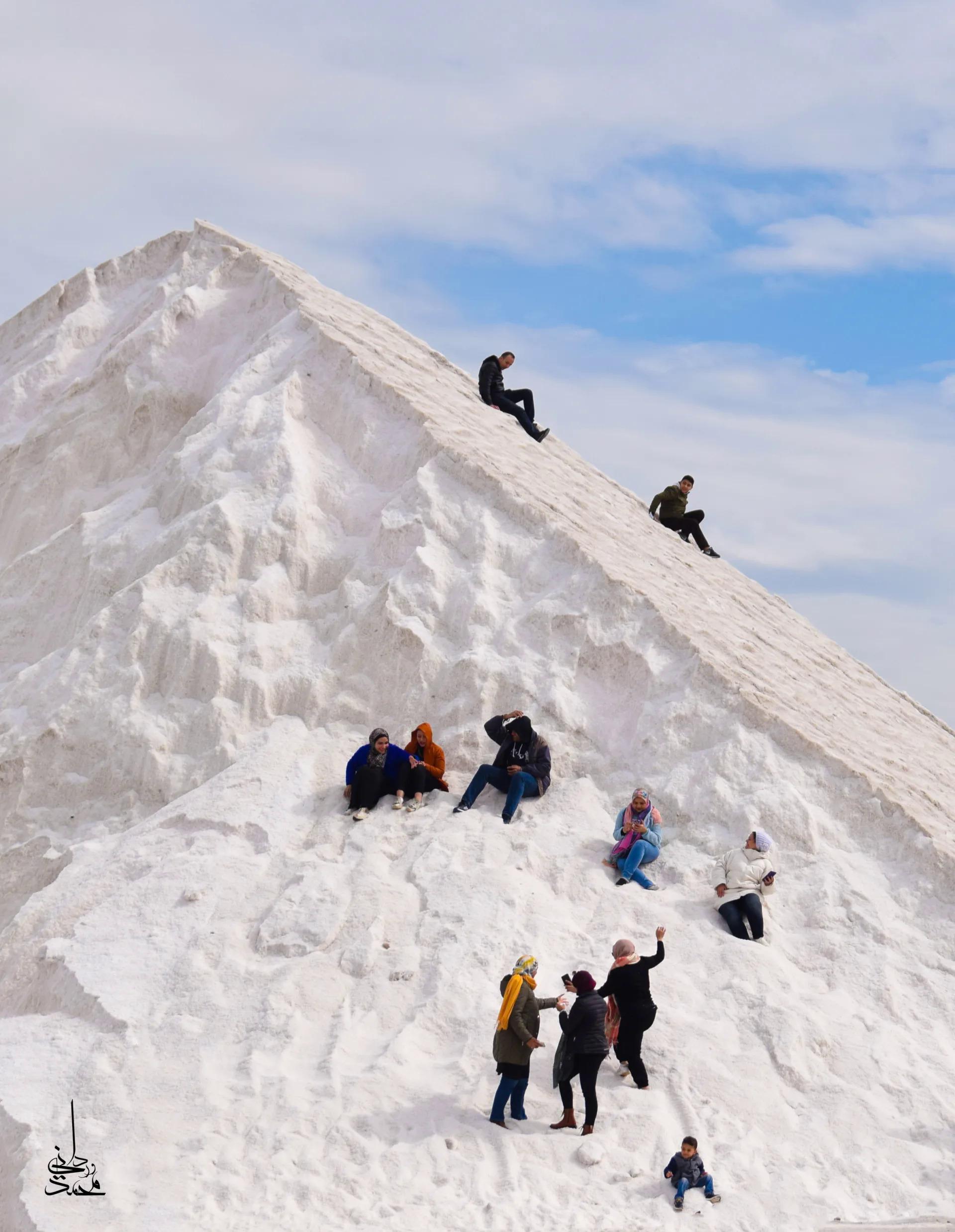 Hình ảnh du khách và người dân tụ tập chơi đùa trước những ngọn núi trắng như tuyết và trượt từ trên đỉnh núi xuống không lạ, tuy nhiên điểm đặc biệt ở đây là khung cảnh này được chụp tại Ai Cập.
