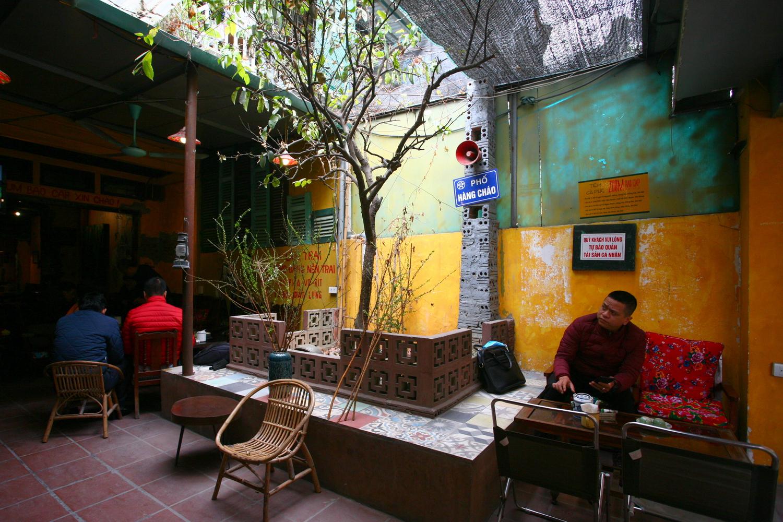 Cà phê Zum bao cấp nằm trên một con ngõ nhỏ ở phố Vũ Ngọc Phan (quận Đống Đa, Hà Nội), trong một căn hộ tập thể tầng 1 đã cũ. Bên ngoài, quán mang vẻ bình dị, gần gũi. Những căn hộ ở tầng trên và xung quanh với những ban công lồng sắt như phụ họa thêm sự cũ kỹ của quán.Không gian quán tịnh tiến theo chiều sâu của căn hộ. Phía ngoài có một khoảng sân nhỏ trồng cây xanh. Kiến trúc của quán gần như được giữ nguyên theo hiện trạng, chỉ làm mới một số bộ phận công năng phục vụ hoạt động cà phê.
