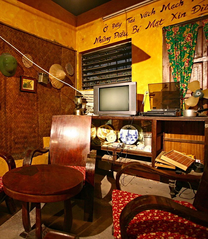 Phòng bên cạnh là một không gian có phần xộc xệch với bức tường cót ép – vật liệu thường dùng làm vách ngăn ở những dãy nhà tập thể xưa. Những vật dụng như mũ cối, mũ lá, bi đông nước, quạt tai voi, máy nghe đĩa than làm không khí thêm màu xưa cũ.