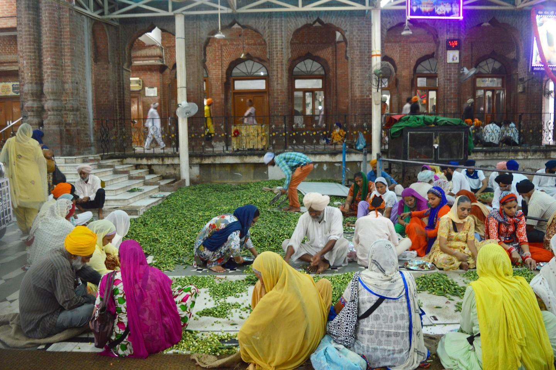 Những tình nguyện viên cùng chuẩn bị cho bữa ăn khổng lồ trong khu bếp cộng đồng. Ảnh: Darshita Thakker