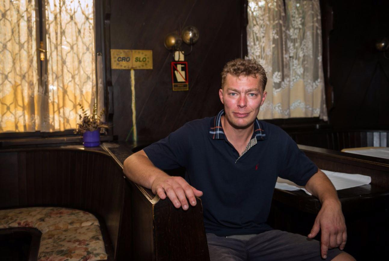 Sasha Kalin ngồi trong quán rượu của mình, phía sau là đường đánh dấu biên giới vẽ trên tường. Ảnh: Sun