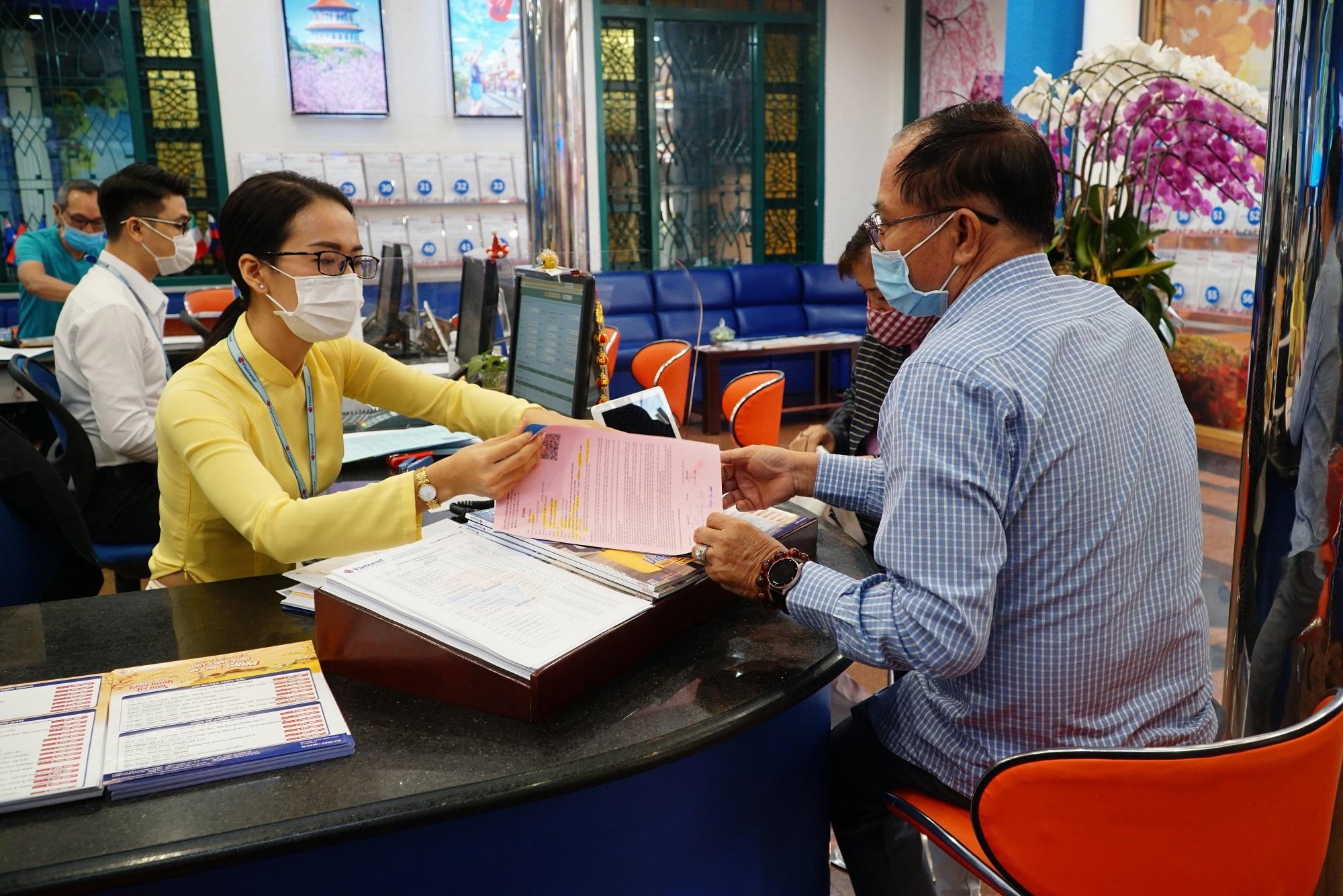 Du khách khi tới các trụ sở của công ty du lịch được yêu cầu sát khuẩn tay, đeo khẩu trang và đo thân nhiệt. Ảnh: Vietravel.