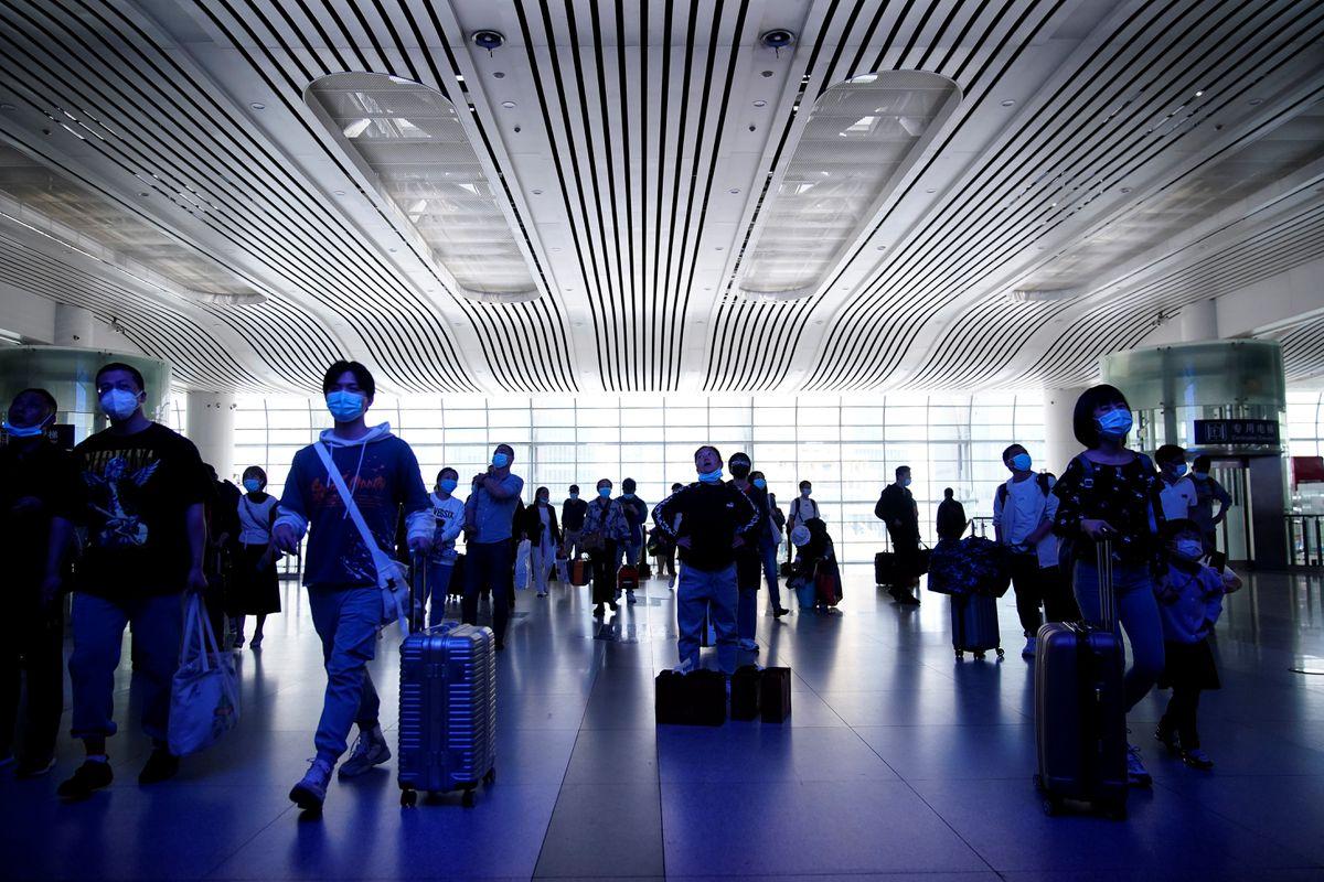 Người dân và du khách đeo khẩu trang di chuyển trong ga tàu Thượng Hải ngày 30/4. Theo số liệu của Ctrip, một cơ quan du lịch trực tuyến hàng đầu Trung Quốc, lượng đặt vé máy bay, khách sạn và điểm tham quan tăng lần lượt 23%, 43% và 114% so với năm 2019.Không giống kỳ nghỉ 3 ngày vào tháng 4, nhiều người chọn đi nghỉ ngắn ngày thì kỳ lễ tháng 5 này đã có 70% du khách đi nghỉ dài ngày tới các tỉnh thành khác. Ảnh: Reuters/Aly Song