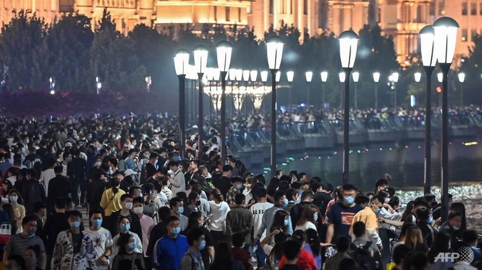 Lượng lớn du khách đeo khẩu trang đổ về dạo chơi ở khu vực bến Thượng Hải dọc sông Hoàng Phố tối 1/5.Không giống kỳ nghỉ 3 ngày vào tháng 4, nhiều người chọn đi nghỉ ngắn ngày thì kỳ lễ tháng 5 này đã có 70% du khách đi nghỉ dài ngày tới các tỉnh thành khác. Ảnh: AFP/Hector Retamal