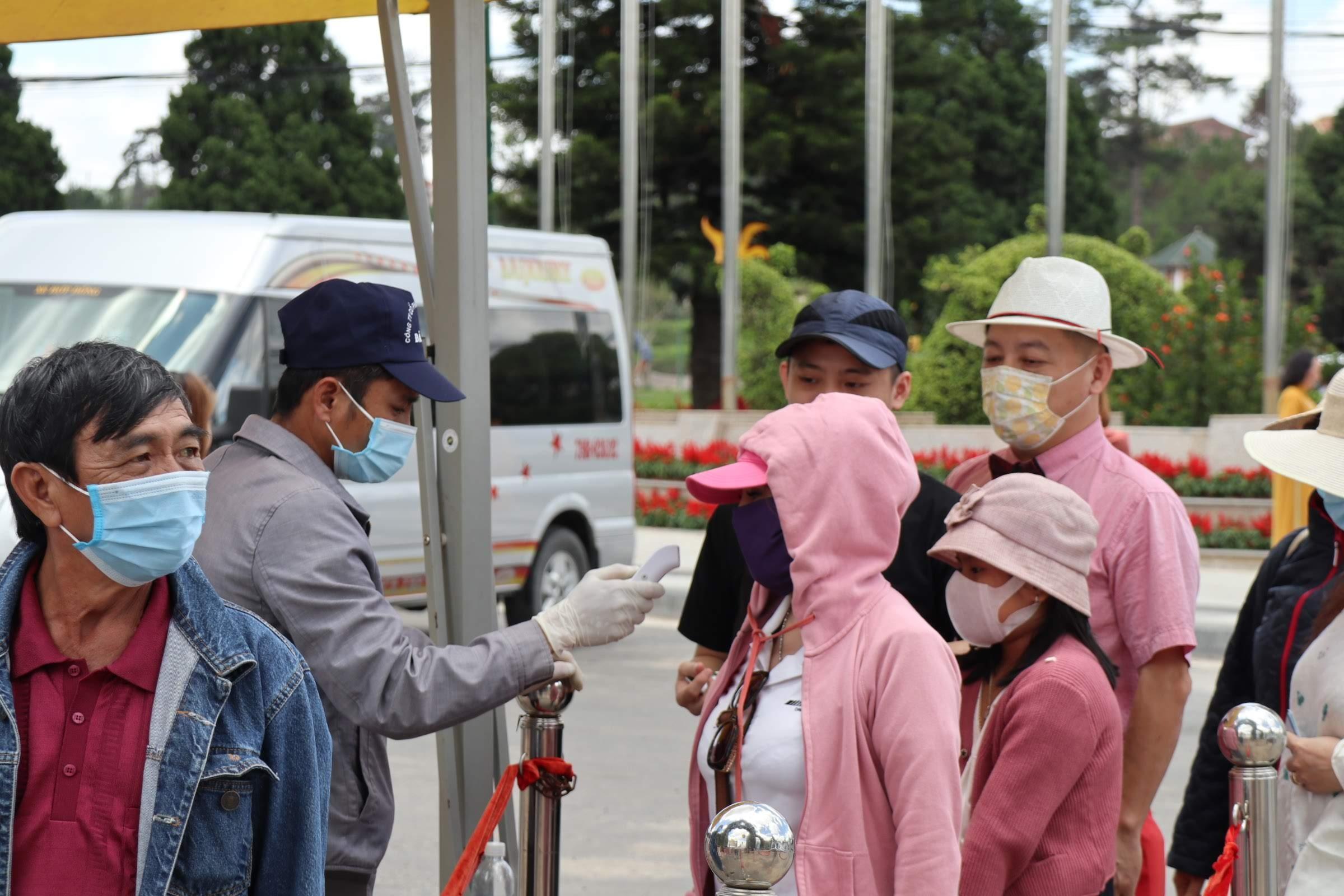 Du khách đo thân nhiệt, thực hiện đeo khẩu trang trước khi vào Vườn hoa thành phố ngày 1/5. Ảnh: Khánh Hương.