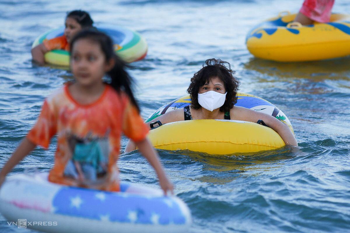 Người dân đeo khẩu trang tắm biển ở Đà Nẵng ngày 29/4. Ảnh: Nguyễn Đông.