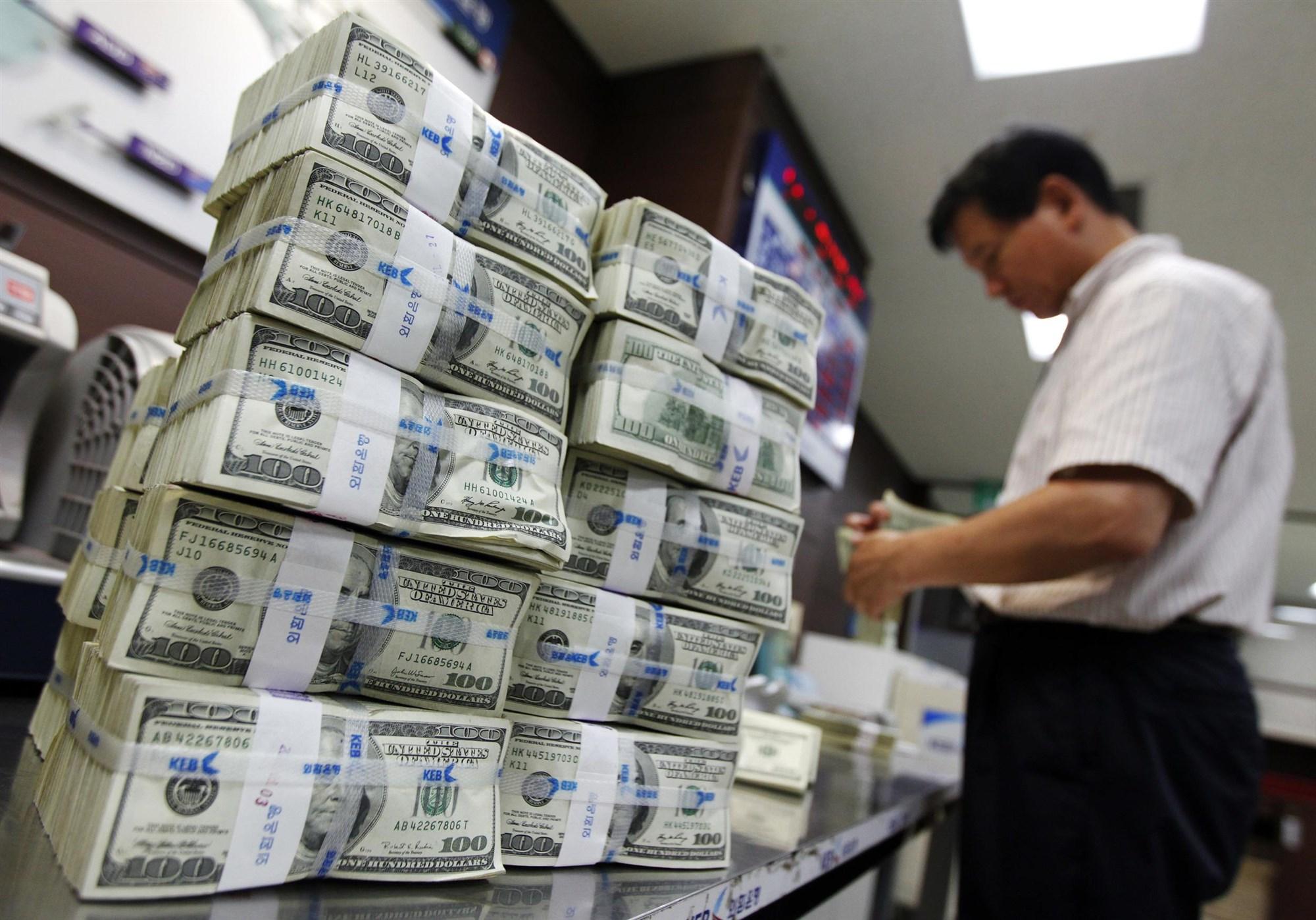 Tiền cùng màu: Thoạt nhìn các đồng USD khá giống nhau, đều có màu xanh, ngoại trừ hình ảnh in trên tiền. Trong khi đó ở nhiều quốc gia khác, các đồng tiền có màu sắc, hình dáng và kích thước khác nhau tùy theo mệnh giá. Do đó, khách du lịch sẽ dễ bối rối khi tiêu tiền USD. Ảnh: Jo Yong Hak/ Reuters