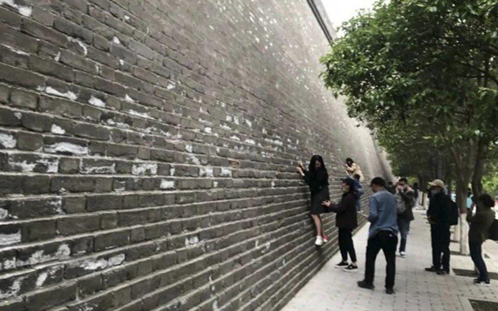 Du khách thi nhau trèo lên các bức tường thành cổ, bất chấp hành động này gây hư hại cho di tích quốc gia. Ảnh: Handout