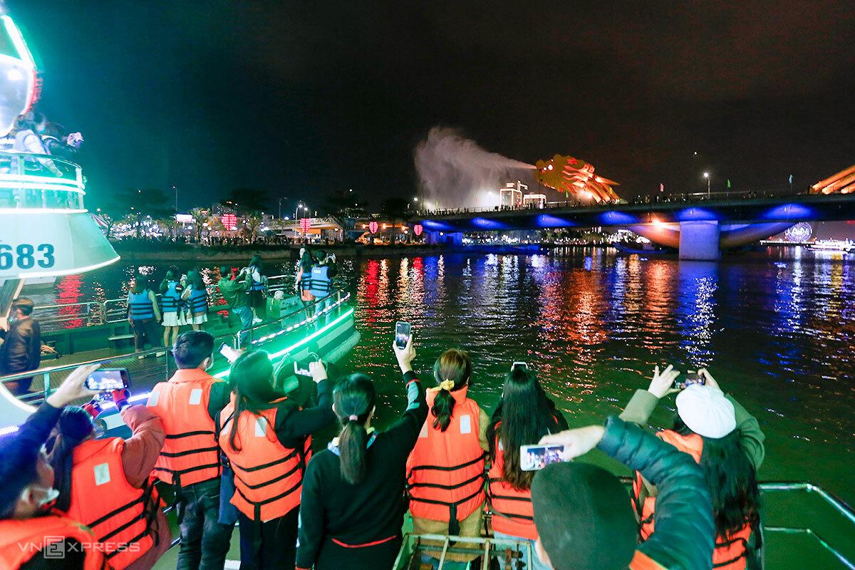 Du khách trải nghiệm đi du thuyền ngắm sông Hàn và cầu Rồng phun lửa, nước, dịp Tết 2021. Ảnh: Nguyễn Đông.