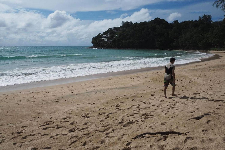 Người đàn ông đi trên bãi biển không một bóng người tại bãi biển Kamala, Phuket. Ảnh: Dusida Worrachaddejchai