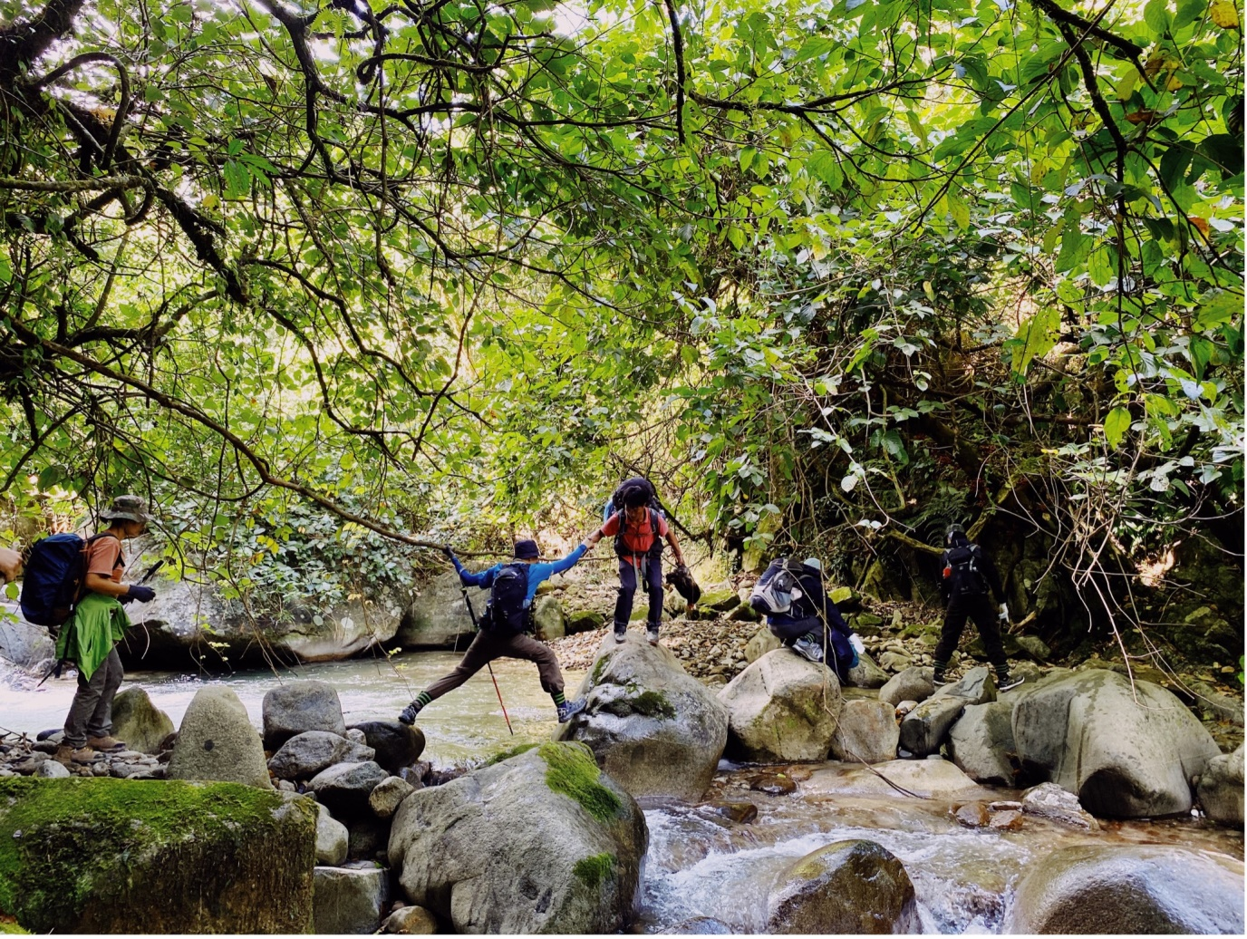 The guide helps the tourists cross the stream.  Photo: Hoang Bac