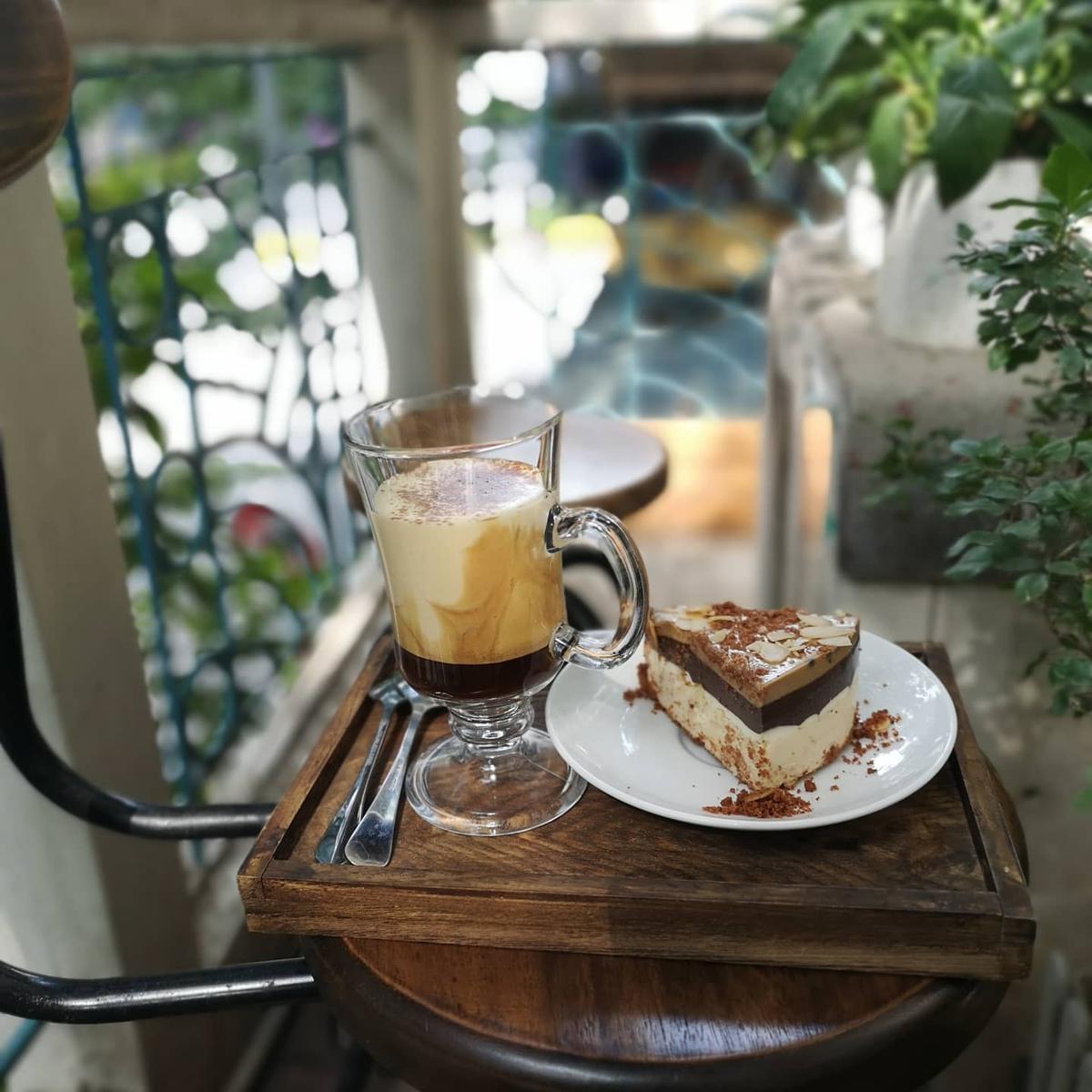 V60+Lối vào quán là cầu thang dốc nhỏ hẹp dẫn lên tầng 2 một căn biệt thự ở 81 Nguyễn Thái Học. Quán có 2 tầng rộng rãi, phong cách cổ điển nhờ cách trang trí gỗ, gạch bông, tường gạch trắng. Ngoài cà phê, V60+ còn là địa chỉ cho những người yêu nhiếp ảnh. Thực đơn cà phê thuần Việt với các loại pha kem trứng, kem sữa và trà hoa, bánh ngọt đi kèm. Mức giá trung bình từ 35.000 đến 50.000 đồng. Quán mở cửa đến 22h30. Ảnh: V60+ Coffee.