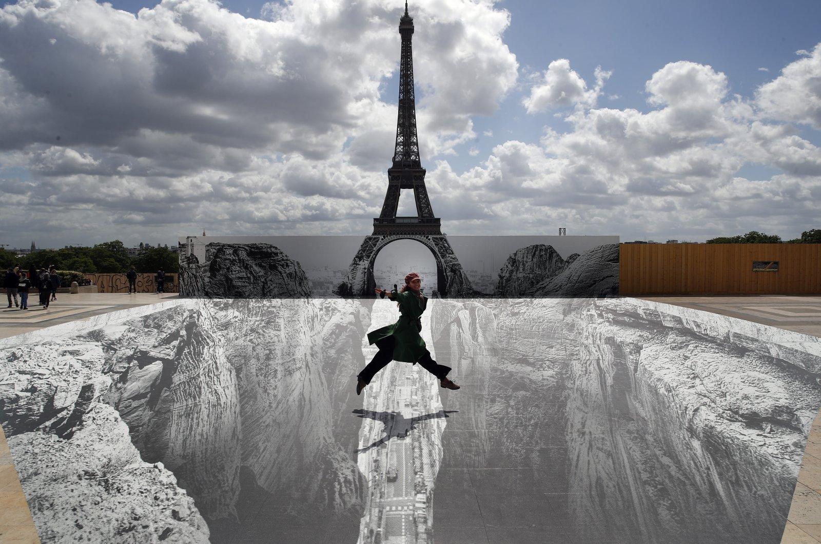 Công trình được dựng tại Paris từ năm 1889, hiện có diện mạo kỳ ảo nhờ tác phẩm 3D khổng lồ của JR. Ảnh: AP