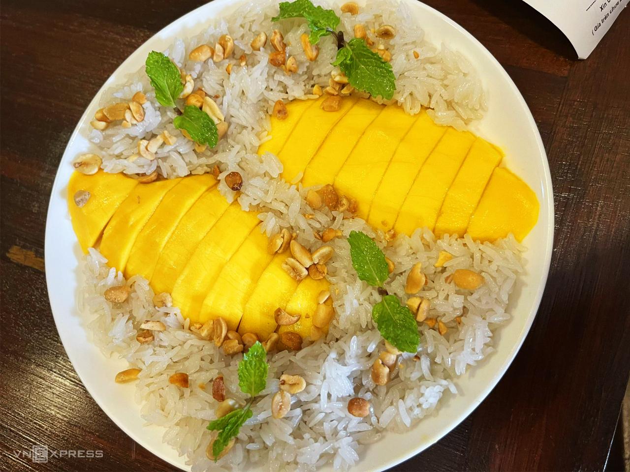 Xôi xoài Thái Lan có thành phần gồm gạo nếp, xoài tươi và nước cốt dừa. Đây là món ăn truyền thống của người Thái, sử dụng giống xoài Thanh Ca, với thịt quả vàng tươi, thơm ngon, chắc mịn và ít xơ. Xôi được hấp cùng hỗn hợp nước cốt dừa và lá dứa tạo ra hương vị béo ngọt, có mùi thơm nhẹ. Đặc biệt, xôi xoài Thái Lan không ăn với đậu phộng mà ăn cùng đậu xanh rang lên, rắc trên bề mặt, ăn kết hợp với nước cốt dừa. Ảnh: Hải Trần