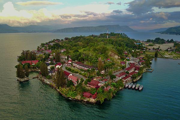 Hòn đảo có lịch sử đáng sợ nhấtĐảo Pulau Samosir nằm giữa hồ Toba, có diện tích gần bằng Singapore. Nơi đây từng được biết đến là một trong những hòn đảo đáng sợ nhất thế giới. Người dân bản địa cổ đại từng là những kẻ săn đầu người đáng sợ. Nhưng hậu duệ của họ, những người Batak đang sống trên đảo lại rất thân thiện, luôn chào đón du khách ghé thăm. Trước đại dịch, đảo là một trong những điểm hút khách khi nhiều người ưa mạo hiểm thường tới đây để bơi trong làn nước êm dịu, và tìm hiểu về văn hóa cổ xưa của người dân địa phương. Ảnh: Toledo Inn Samosir