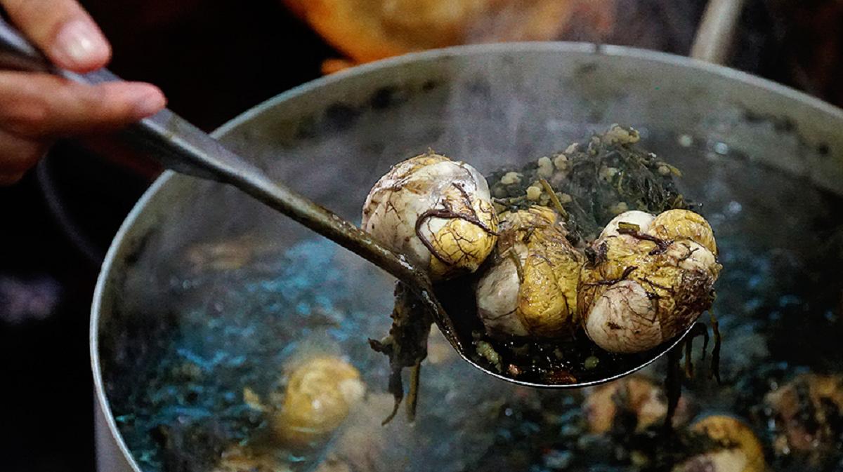 Ở Hải Phòng hay Hà Nội cũng có cách ăn trứng vịt lộn hầm ngải cứu và huyết. Đầu bếp chọn lá ngải cứu xanh non rửa sạch với nước. Trứng vịt lộn được luộc chín trước khi đem hầm với lá ngải cứu trên bếp chừng 2-3 giờ là có thể ăn được, gia vị đi kèm là gừng được cạo vỏ, rửa sạch cắt sợi. Ăn món này không thể thiếu măng ngâm chua tạo cảm giác đỡ ngấy, thực khách có thể thêm tương ớt hoặc tắc (quất) để tăng gia vị. Ảnh: Di Vỹ