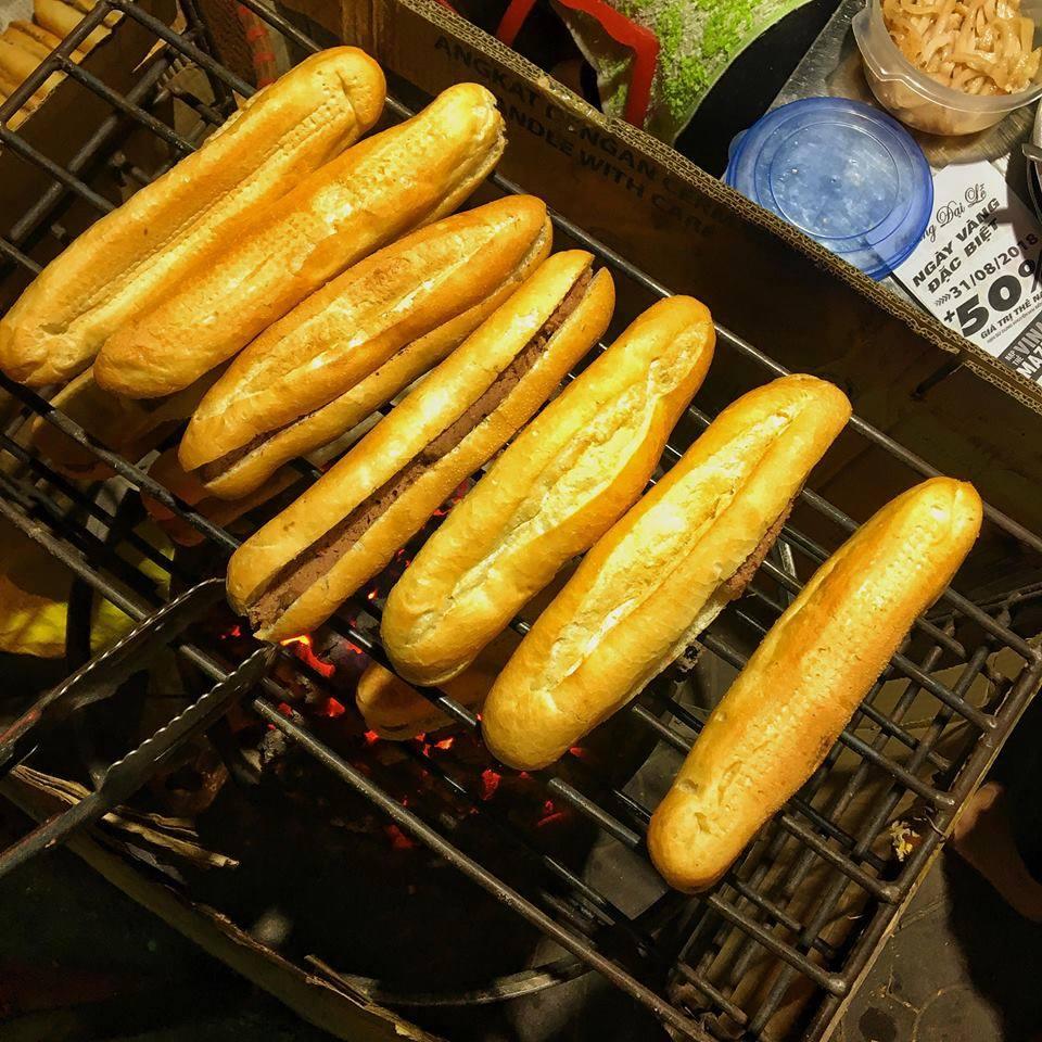Hải Phòng nổi tiếng với bánh mì que, thường có kích thước bằng 2-3 ngón tay gộp lại, vỏ giòn không dày lõi. Bánh mì que có nhân pate kèm sốt ớt cay nồng hoặc nhân bơ sữa. Bánh thường được nướng than trước khi rưới mỡ giúp vỏ giòn xốp hơn. Ảnh: Hoa Cỏ Dại.
