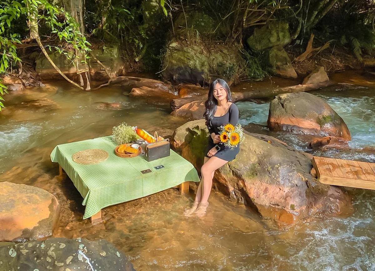 Khách ngồi dưới suối nhâm nhi cà phê, cảm nhận dòng nước mát lạnh đang chảy dưới chân. Ảnh: Khánh Uyên