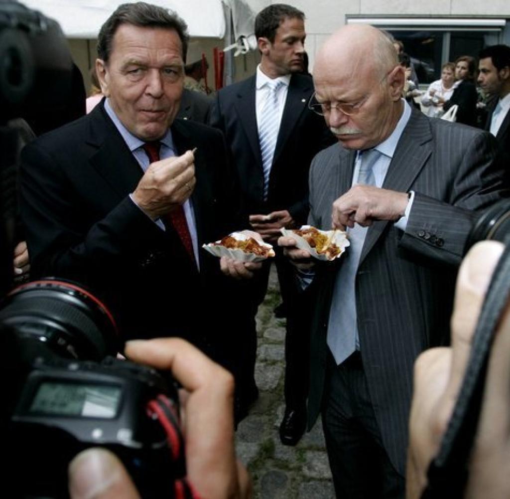 Cựu thủ tướng Gerhard Schroeder (trái) cũng được biết đến là một người hâm mộ lớn của món ăn này. Một sự thật thú vị về món ăn này nữa là theo truyền thống, mọi ứng viên cho chức thị trưởng Berlin đều được chụp ảnh tại một quầy bán currywurst. Ảnh: Welt