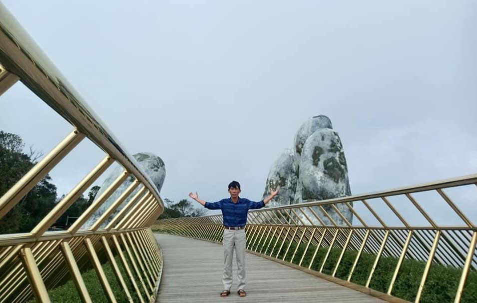 Ông Trung chụp ảnh lưu niệm ở Cầu Vàng, Đà Nẵng tháng 11/2020.