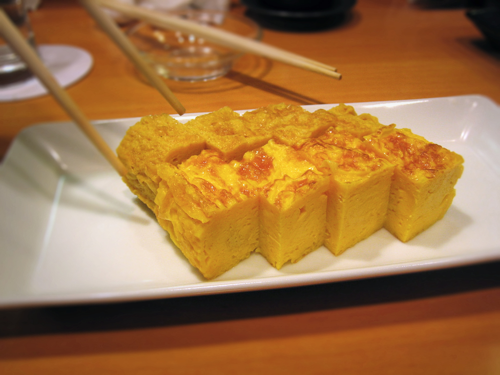 Tamagoyaki là món trứng chiên (hoặc nướng) của Nhật Bản. Đó được cuộn vuông vắn thành nhiều lớp trên chảo rán chuyên dụng có tên makiyakinabe . Món ăn này có thể có nhiều vị khác nhau như mặn, ngọt. Nguyên liệu cơ bản cho Tamagoyakilà trứng, đậu nành, đường và nước dashi. Ảnh: Flickr
