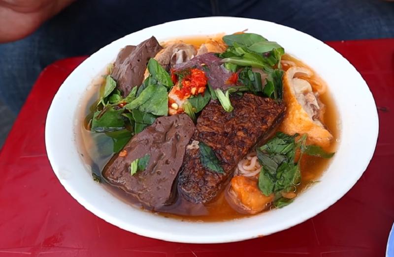 Bún riêu vịt trông đầy đặn với phần thịt vịt luộc vàng, huyết và rau thơm phủ đầy. Gọi bún riêu nhưng thành phần món ăn không có riêu cua, nước dùng nấu từ thịt vịt, ruốc khô, cà chua nêm nếm vừa miệng, mộc mạc. Thịt vịt được thực khách nhận xét nhiều nạc, luộc nềm, làm kỹ không có mùi hôi, chấm cùng nước mắm gừng càng thêm đậm đà. Tô bún có 2 loại huyết ăn kèm, riêng huyết nếp nóng hổi, giòn bên ngoài, dẻo bên trong ăn lạ miệng. Thực khách có thể gọi thêm chân vịt, đầu hoặc cánh tùy theo sở thích. Ảnh: PM FOOD TRAVEL/YouTube