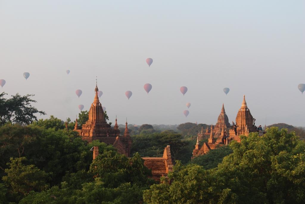 Khinh khí cầu bay lơ lửng trên những ngôi đền tháp ẩn sau rừng cây.