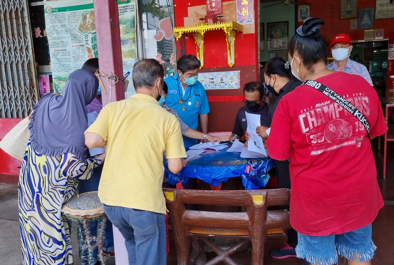 Các HDV khó khăn đến nhận gạo hỗ trợ tại đền Jee Kong Khlong Pom nằm ở trung tâm thành phố. Ảnh:
