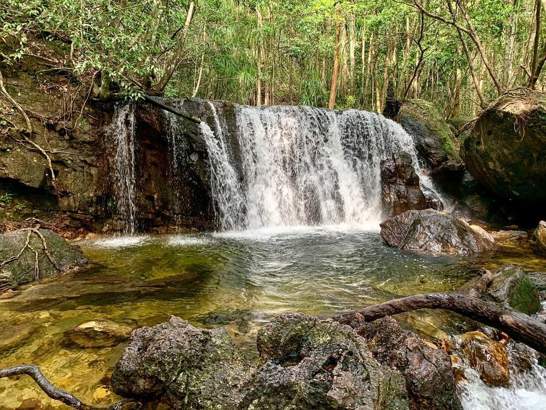 Từ cổng Khu Du lịch Suối Tranh Phú Quốc, du khách đi qua đường mòn lát những viên đá nhỏ, sau khoảng 30 phút đi bộ, bạn sẽ gặp một ngọn thác cao khoảng 2 m. Dưới chân thác, nước đọng lại thành một hồ nước trong và mát rượi, du khách có thể tắm mát, vui chơi tại đây. Ảnh: @ibruque/Instagram