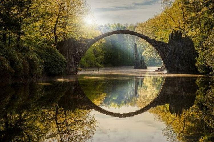 Trên ảnh là cầu Quỷ (Rakotzbrücke) ở Đức. Khi bạn mới nhìn, có vẻ như thiên nhiên đã tạo ra một vòng tròn hoàn hảo giữa hồ nước thơ mộng trong công viên Kromlauer. Nhưng khi lại gần hơn, bạn sẽ nhận ra vòng tròn ấn tượng này là kết quả của một ảo ảnh quang học độc đáo. Cây cầu hình vòm có tên Rakotzbrücke còn được mệnh danh là Cây cầu của quỷ đã khéo léo đánh lừa thị giác của bạn. Công trình được xây dựng bằng đá bazan vào năm 1860 do KTS Friedrich Hermann Rötschke thiết kế. Ảnh: Reddit