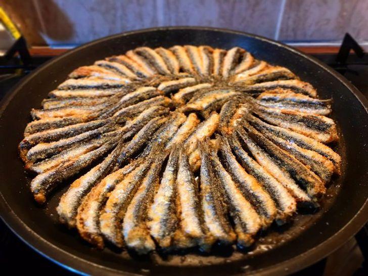 Hamsi tavaĐây là món cá cơm chiên giòn tẩm bột ngô, ăn cùng rau arugula và hành tây cắt lát trong một chiếc bánh mì giòn mới nướng (được gọi là Hamsi Ekmek)Cá cơm chiên giòn tẩm bột ngô. Nếu nó được phục vụ với rau arugula và hành tây cắt lát mỏng trong một chiếc bánh mì giòn mới nướng, nó được gọi là Hamsi Ekmek.  Nên thử ở đâu: Hamsa là một loại cá mùa đông và nó chỉ có sẵn (tươi) từ tháng 11 đến tháng 2. Hãy đến chợ cá ở  Fethiye hoặc đến Nhà cá Karaköy ở Istanbul để thưởng thức món ăn này.What it is made from:Deep-friedanchovies breaded in cornmeal. If it is served with arugula and thinly sliced sweet onions in a freshly-baked, crispy bun, it is called Hamsi Ekmek.  Where to try it:Hamsa is a winter fish and it is available (fresh) only from November to February. Go to the fish market in Fethiyeor to the Istanbul Karaköy Fish House to enjoy this dish.