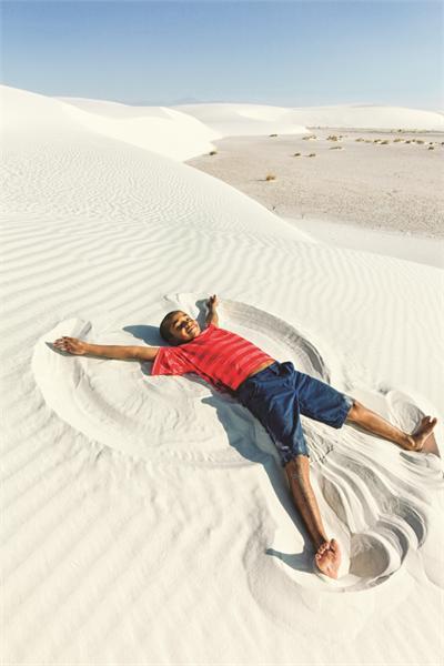 Cậu bé đang tạo hình thiên thần tuyết phiên bản cát thạch cao. Ảnh: New Mexico True