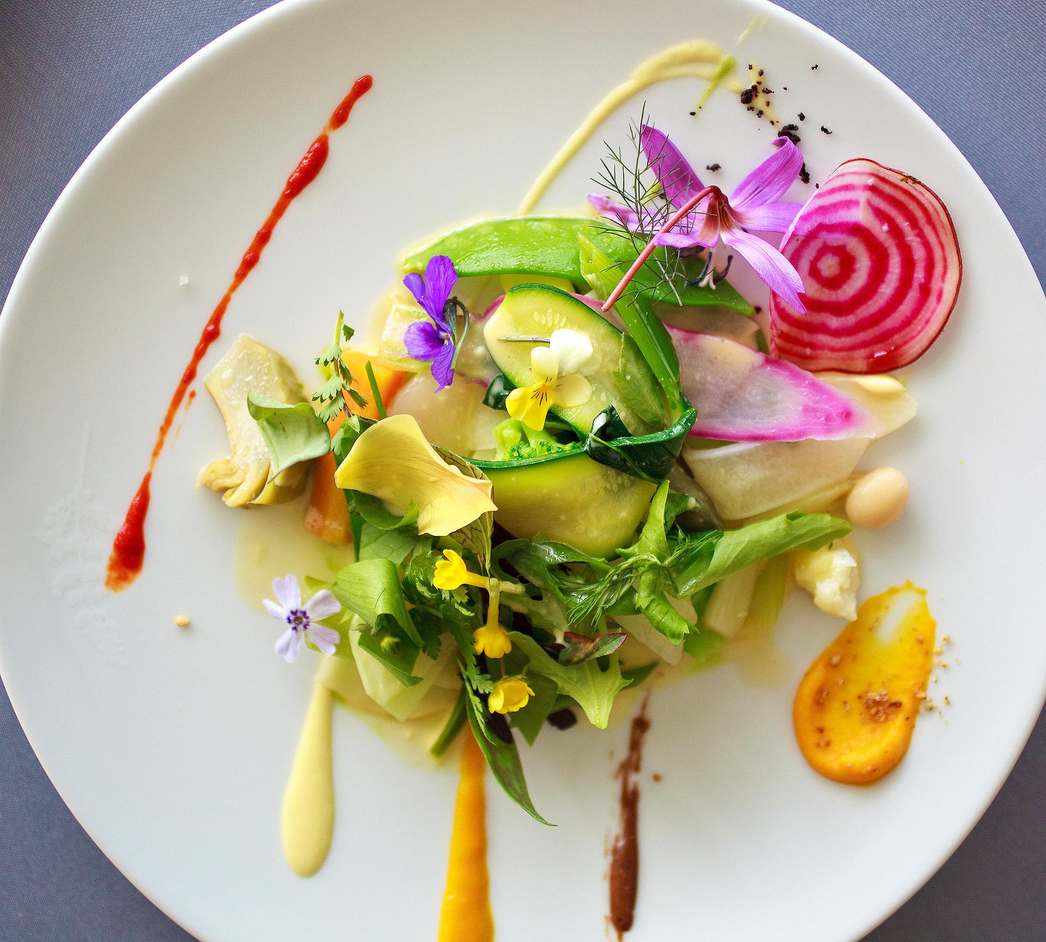 Tại các nhà hàng cao cấp, mỗi món ăn đều được đầu bếp trang trí như một tác phẩm nghệ thuật trước khi mang ra phục vụ khách. Trên ảnh là món ăn Pháp có tên Gargouillou, gồm ít nhất 16 loại rau được nấu riêng rồi sắp xếp lại trên đĩa sao cho đẹp mắt. Nếu là một đĩa đầy rau, thay vì một phần nhỏ, đầu bếp sẽ không thể trang trí chúng một cách đầy nghệ thuật như thế này.Có một món ăn Pháp tên là Gargouillou , bao gồm ít nhất 16 loại rau khác nhau, được nấu riêng biệt. Chiếc đĩa được sắp xếp như một tác phẩm nghệ thuật và chắc chắn sẽ gây ấn tượng với bất kỳ khách hàng nào nhìn thấy tấm bạt đáng kính này trên đĩa. Hãy tưởng tượng bạn đang cố gắng sắp xếp đẹp mắt tất cả những loại rau nhỏ bé này trên một chiếc đĩa đã đầy ắp. Nó có thể sẽ không đẹp về mặt thẩm mỹ như trong hình. Vì vậy, các đầu bếp thích giảm khẩu phần ăn hơn.